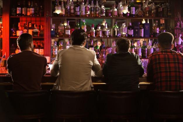 Achteraanzicht van vier jonge mannen bier drinken Gratis Foto