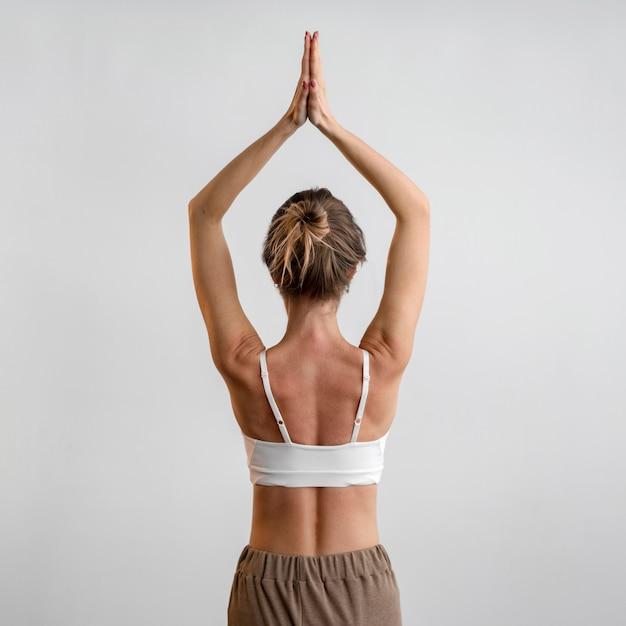 Achteraanzicht van vrouw beoefenen van yoga thuis Gratis Foto