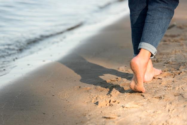 Achteraanzicht van vrouw blootsvoets lopen op het strand Gratis Foto