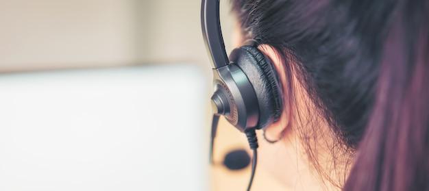 Achteraanzicht van vrouw consultant microfoon headset van klant ondersteuning telefoon operator op werkplek dragen. Premium Foto