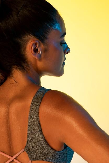 Achteraanzicht van vrouw en gele achtergrond Gratis Foto