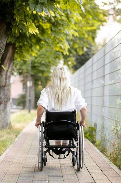 Achteraanzicht van vrouw in rolstoel in de stad Gratis Foto
