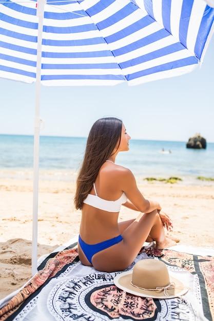 Achteraanzicht van vrouw met gebruinde huid poseren op strand in zonnige dag. portret van achterkant stijlvolle meisje in blauwe bikini, zittend onder parasols op zee achtergrond. Gratis Foto