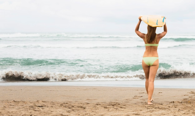 Achteraanzicht van vrouw met surfplank op het strand Gratis Foto