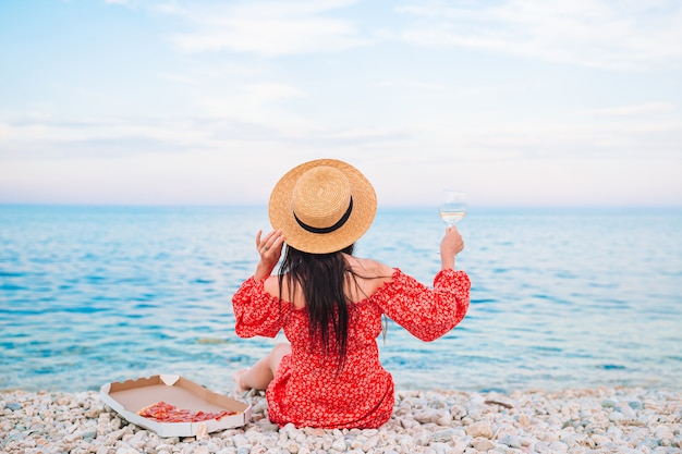 Achteraanzicht van vrouw op het strand op picknick met een glas wijn en pizza Premium Foto