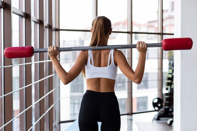 Achteraanzicht van vrouw training met gewichten bar Gratis Foto