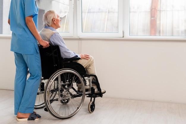 Achteraanzicht verzorger en oude man kijkt op het raam Gratis Foto
