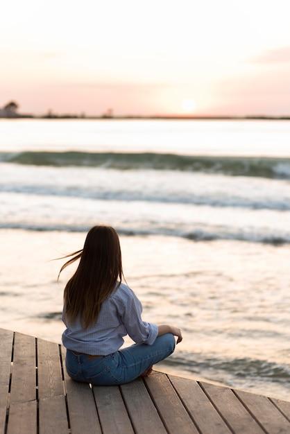 Achteraanzicht vrouw buiten mediteren Gratis Foto