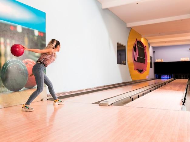 Achteraanzicht vrouw gooien bowlingbal Gratis Foto