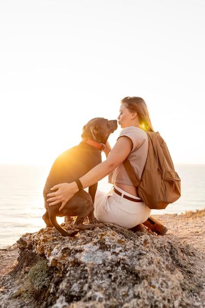 Achteraanzicht vrouw haar hond knuffelen bij zonsondergang Gratis Foto