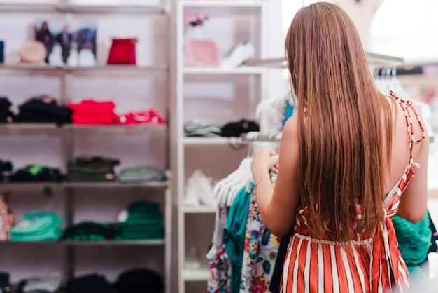 Achteraanzicht vrouw kijken naar kleding Gratis Foto
