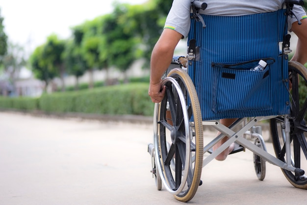 Achterbeeld van de bejaardenrolstoel tijdens een wandeling in het park Premium Foto