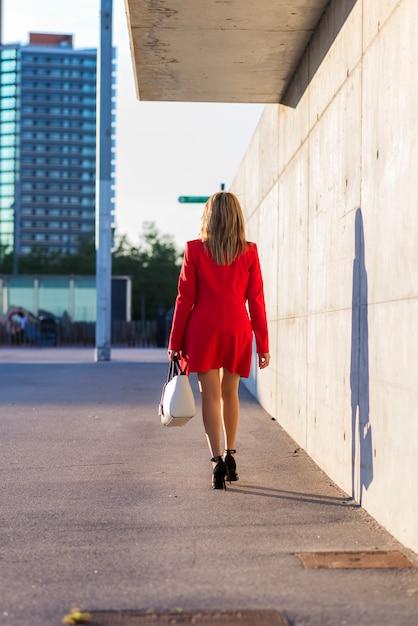 Achterbeeld van een blondevrouw die rode jasje witte handtas dragen terwijl het lopen in de stad Premium Foto