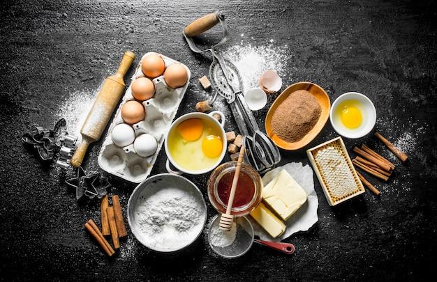 Achtergrond bakken. ingrediënten om thuis koekjes te maken. op zwarte rustieke achtergrond Premium Foto