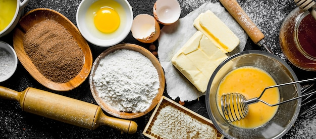 Achtergrond bakken. ingrediënten voor het maken van zelfgemaakte koekjes. op zwarte rustieke achtergrond Premium Foto