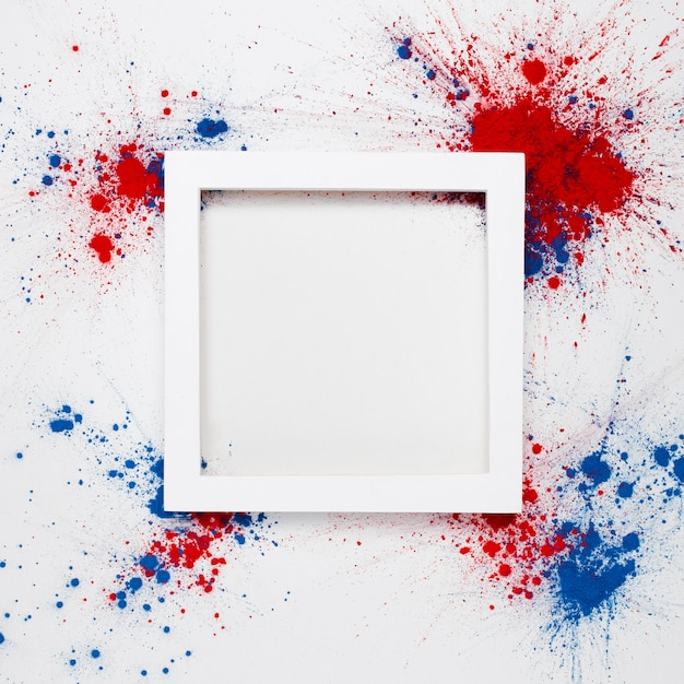 Achtergrond met een wit frame met copyspace en vuurwerk gemaakt met spatten van holi kleur Gratis Foto