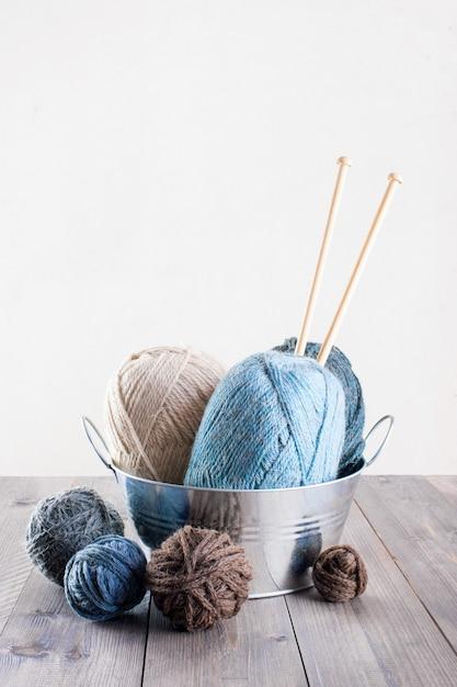 Achtergrond met wol en breinaalden op de houten tafel Premium Foto