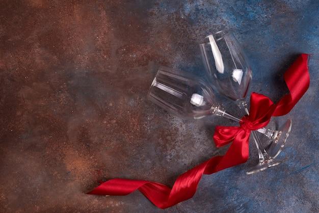 Achtergrond van de viering van de valentijnskaartendag met twee glazen en rood lint Premium Foto
