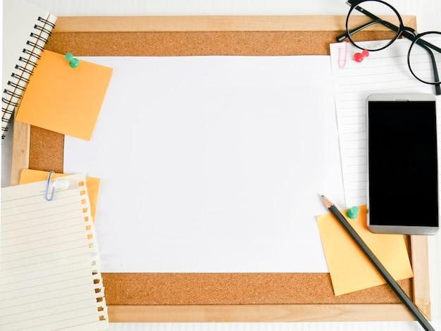 Achtergrond van een houten bord, briefpapier, blanco papier met apparatuur rond, zoals potloden, glazen, geld, mobiele telefoons en kalenders, Premium Foto