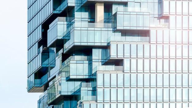 Achtergrond van moderne blauwe het glasverglazing van de de bouwarchitectuurmuur in patroonkubus en vierkante overlapping met verlichtingszonlicht Premium Foto
