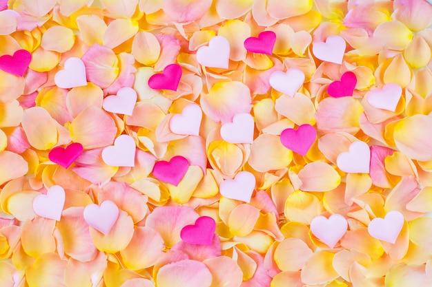 Achtergrond van roze rozenblaadjes veelkleurige harten van satijn Premium Foto
