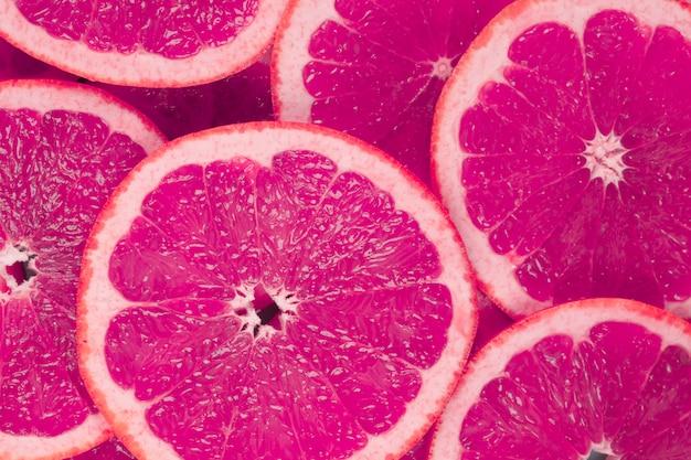 Achtergrond van sappige grapefruits plakjes Gratis Foto