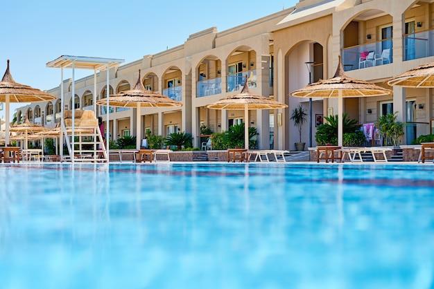 Achtergrond van water in blauw zwembad, waterspiegel met een zonbezinning Premium Foto