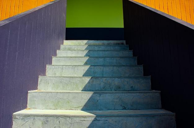 Achtergrond van zonlicht en schaduw op de witte oppervlakte van steenstappen van kleurrijke trap in lage hoek en perspectiefmening, beeld voor het ontwerpconcept van de huisbuitendecoratie. Premium Foto
