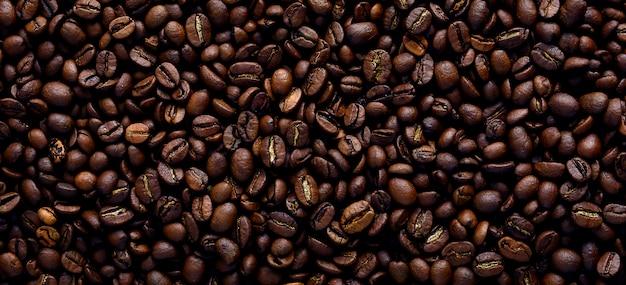Achtergrondtextuur van een reusachtig aantal geurige en verse bruine geroosterde koffiebonen. een van de fasen van het maken van natuurlijke koffie Premium Foto