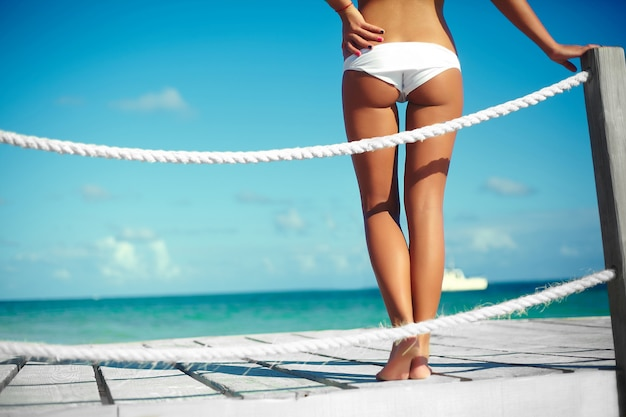 Achterkant glamour zonovergoten vrouw in witte lingerie op een pier Gratis Foto