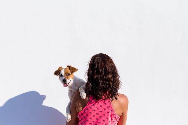 Achterkant van een vrouw met een schattige kleine hond over een witte muur. zonsondergang in een zomerse dag. Premium Foto