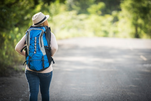 Achterkant van jonge vrouw die backpacker op bosweg en het bekijken rond aard lopen. Gratis Foto