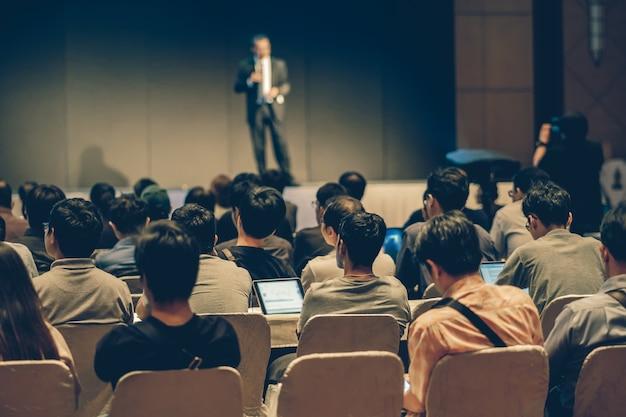 Achterkant van publiek zittend en luisterend naar de sprekers Premium Foto