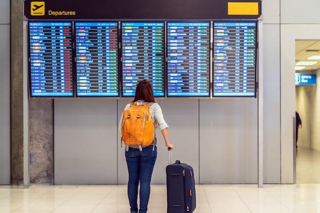 Achterkant van reiziger met bagage die zich over de vluchtraad bevindt voor controle Premium Foto