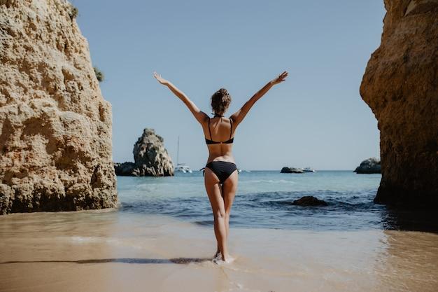 Achterkant weergave meisje in zwembroek met sexy billen staat op grote steen op het strand tijdens zonsondergang. Gratis Foto