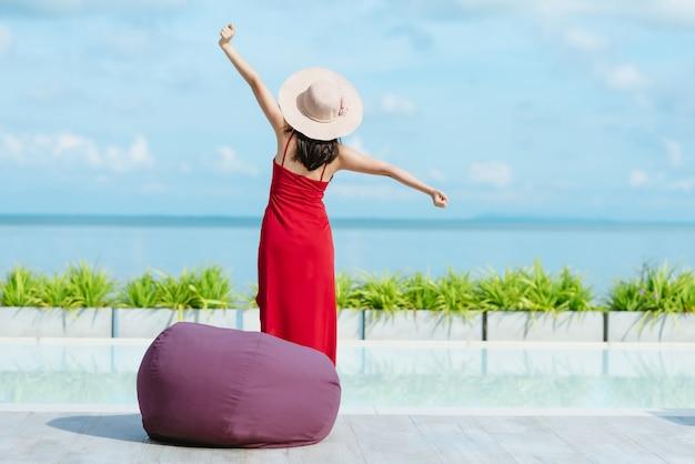 Achtermening die van vrouw en zich door zwembad uitrekken ontspannen Premium Foto
