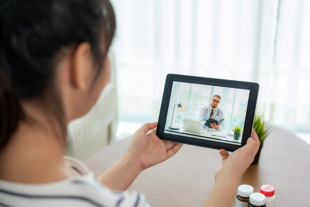 Achtermening die van vrouw videogesprek met haar arts maken terwijl thuis het blijven. Premium Foto