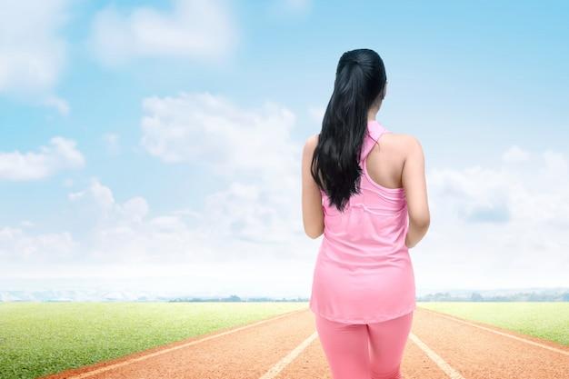 Achtermening van aziatische agentvrouw die op de renbaan lopen Premium Foto