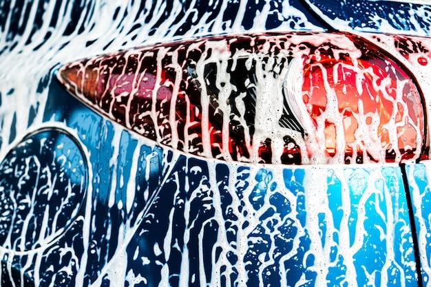 Achtermening van blauwe compacte suv-auto met sport en moderne ontwerpwas met zeep. Premium Foto