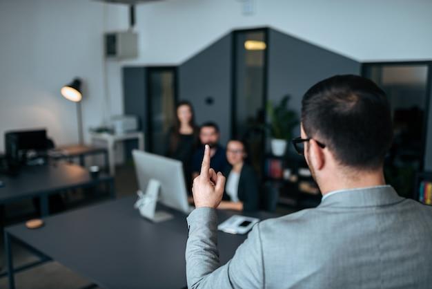 Achtermening van de bedrijfsmens die aan collega's op commerciële vergadering spreken. Premium Foto