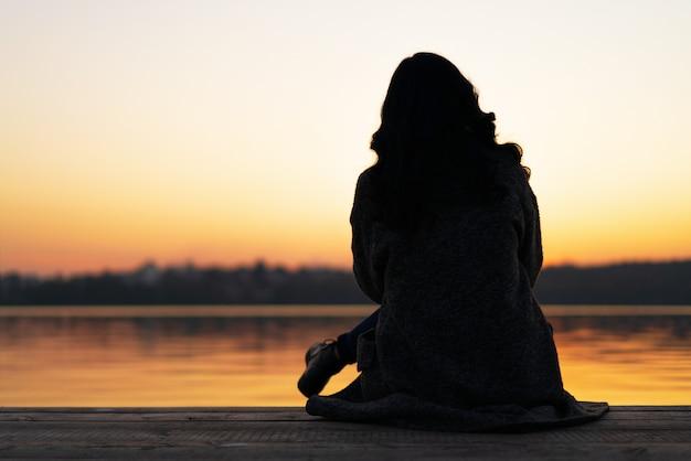 Achtermening van de lange zitting van het haar donkerbruine meisje op de pijler dichtbij meer in zonsondergangtijd. Premium Foto