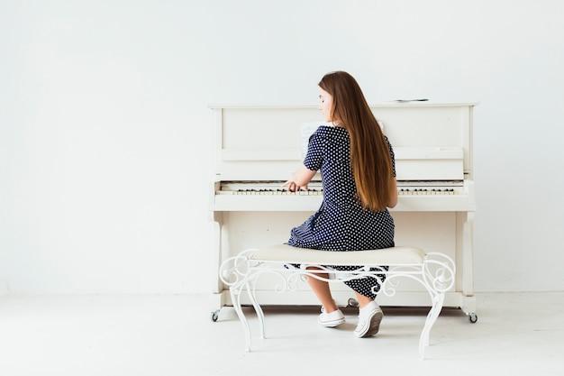 Achtermening van een jonge vrouw met lang haar die de piano spelen tegen witte muur Gratis Foto