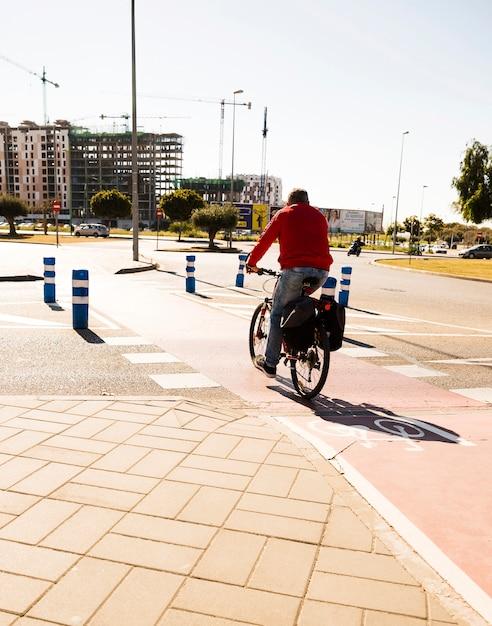 Achtermening van een mens die de fiets berijden op straat in de stad Gratis Foto