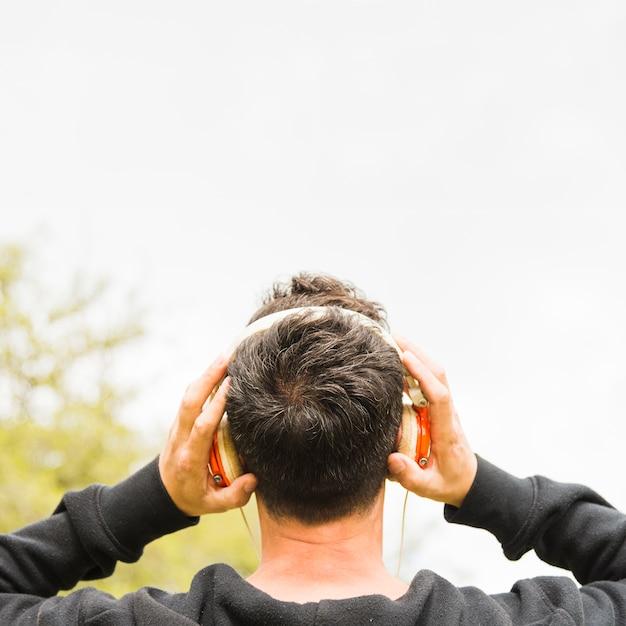 Achtermening van een mens het luisteren muziek op hoofdtelefoon in openlucht Gratis Foto