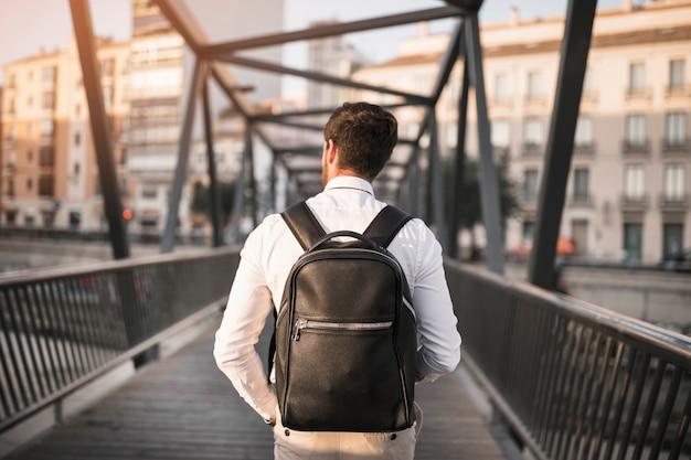 Achtermening van een mens met zwarte rugzak die zich op brug bevinden Gratis Foto