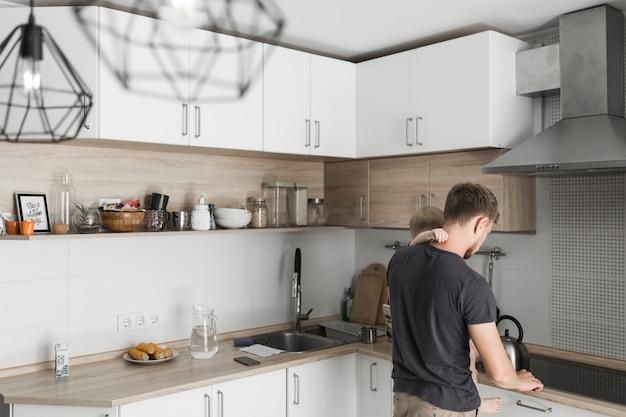 Achtermening van een vader die zijn zoon vervoert die in de keuken werkt Gratis Foto