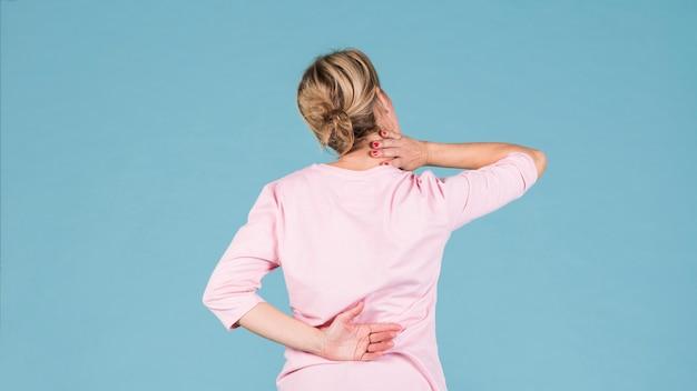 Achtermening van een vrouw die aan rugpijn en schouderpijn lijden Gratis Foto