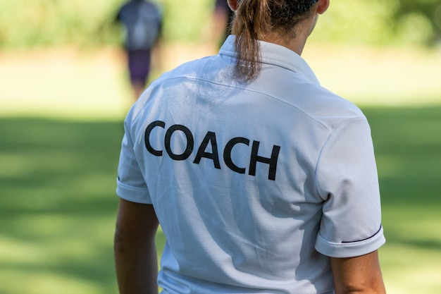 Achtermening van een vrouwelijke sportbus die op haar team letten concurrerend bij een openluchtsportgebied Premium Foto