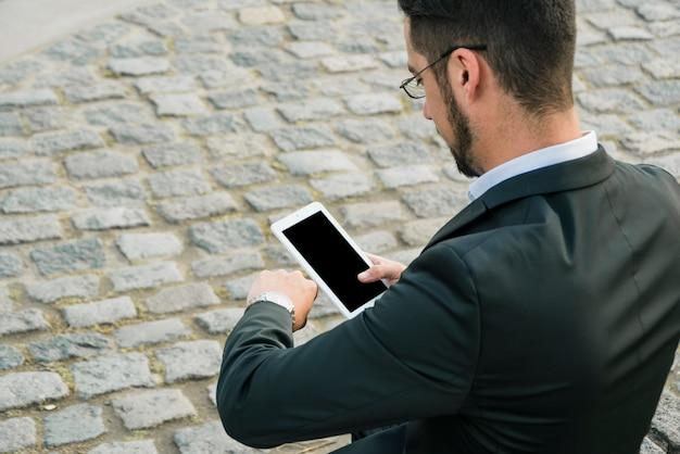 Achtermening van een zakenman die zich op de bestrating bevinden die mobiele in hand houden die de tijd controleren Gratis Foto