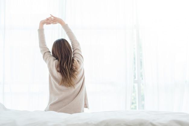 Achtermening van gelukkige mooie jonge aziatische vrouwenontwaken in ochtend, die op bed zitten Gratis Foto